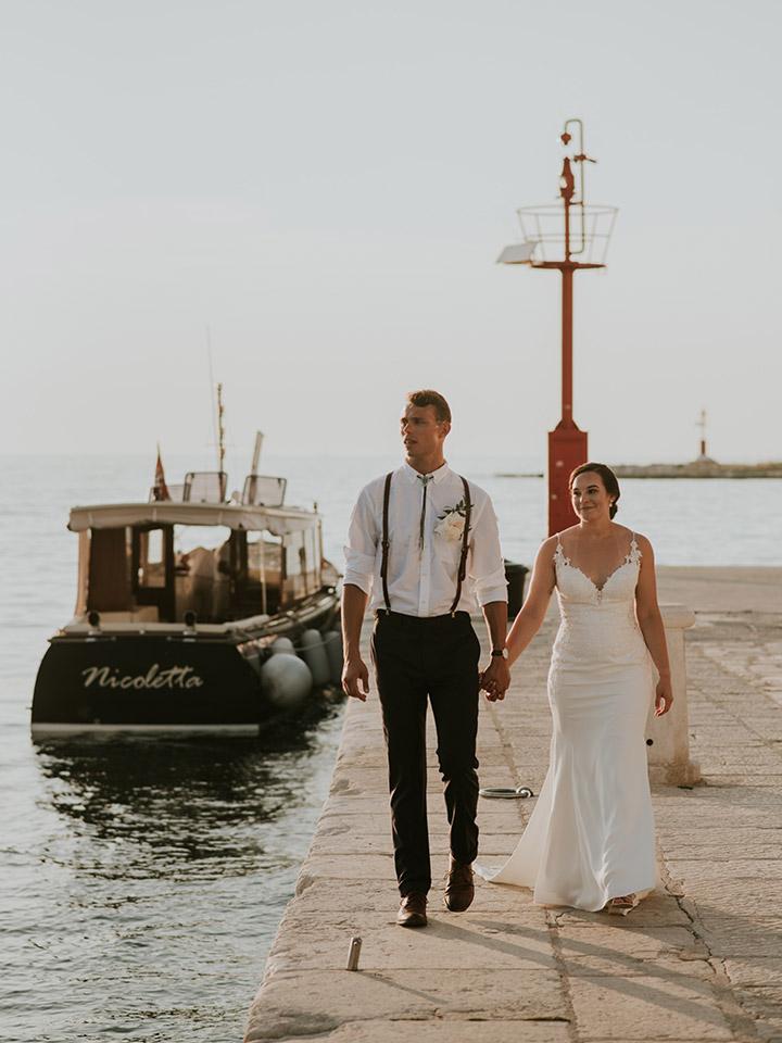Newlyweds walking alone by the sea.