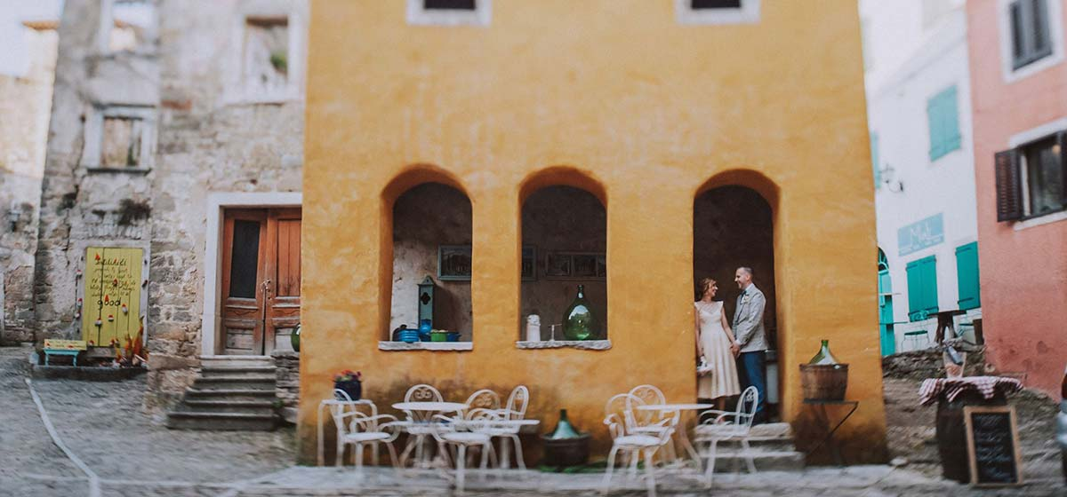 Mladenci poziraju za fotografiju ispred žutog restorana.