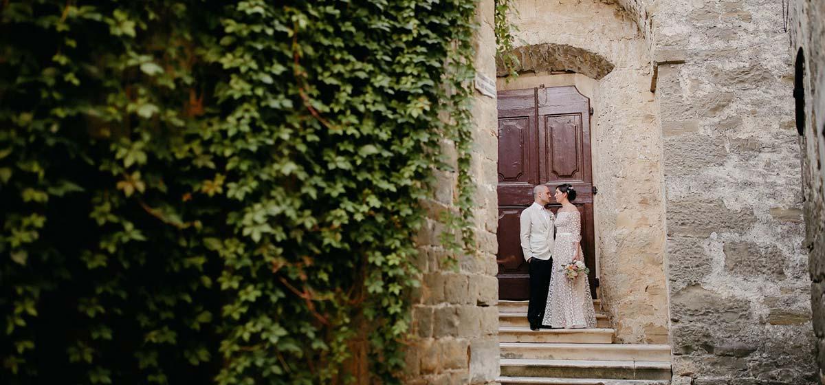 Mladenci stoje ispred crkve u kojoj je održana njihova vjenčana ceremonija u Hrvatskoj.