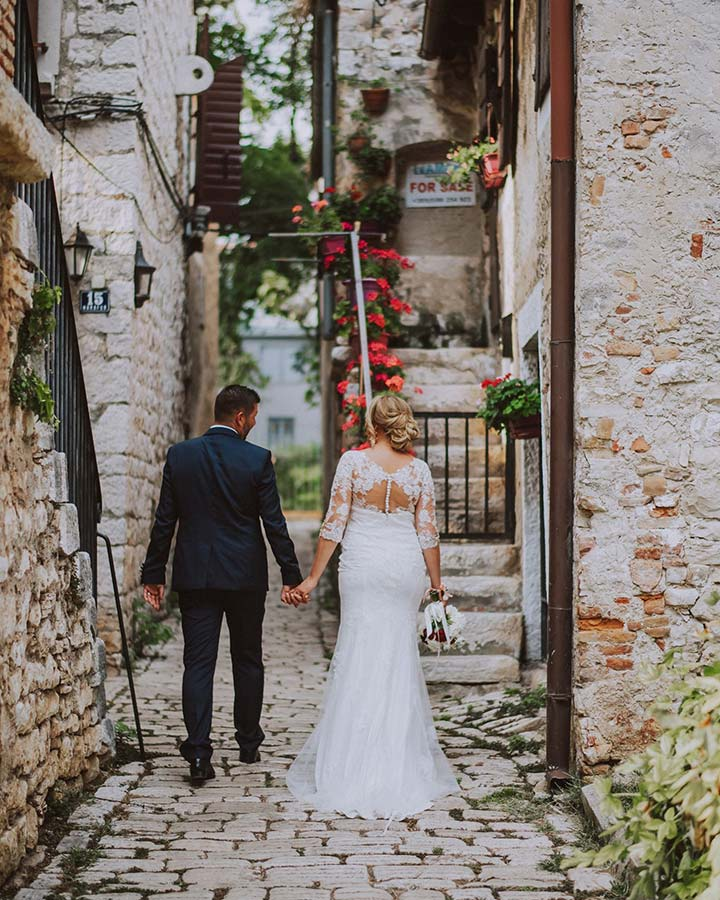 Mladenci se na uskoj kaldrmi u Poreču fotografiraju za svoj album vjenčanja u Hrvatskoj.