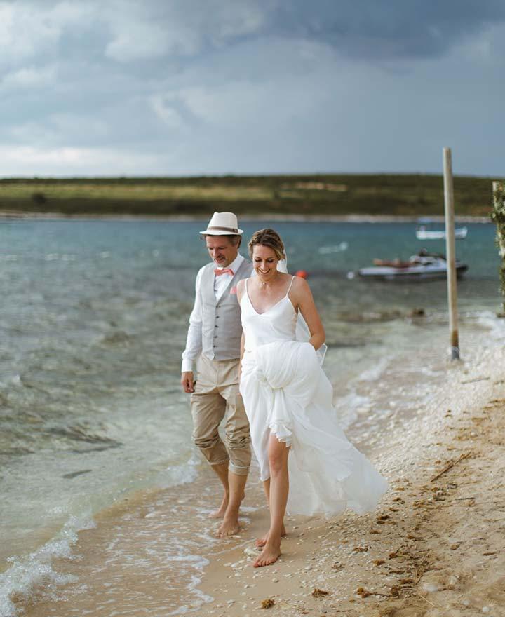 Mladenci hodaju duž plaže nakon njihovog vjenčanja u Hrvatskoj.