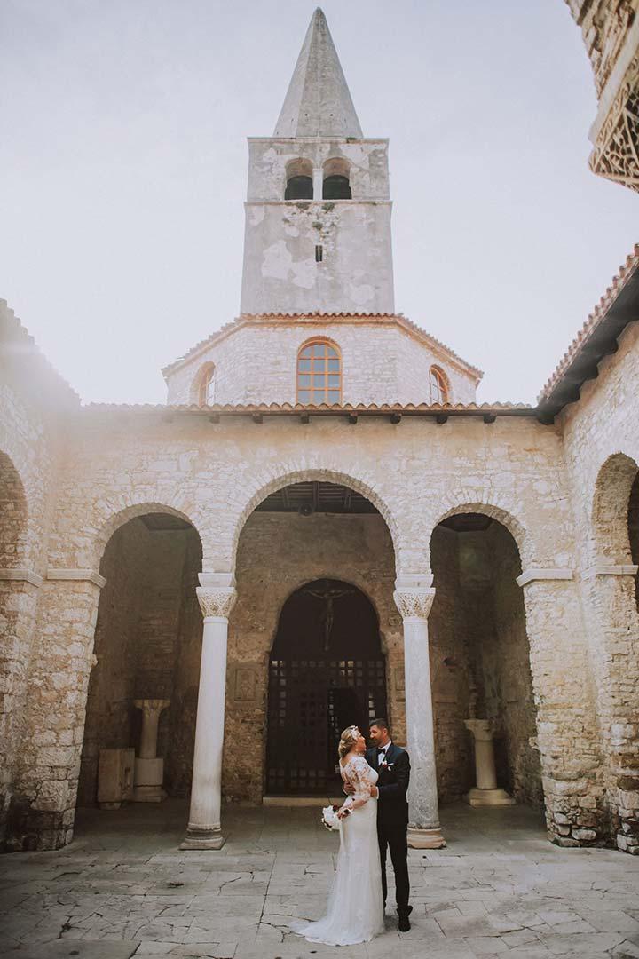 Mladenci se grle u atriju stare crkve u Istri. Ova crkva je savršena lokacija za održavanje vjenčane ceremonije u Hrvatskoj.