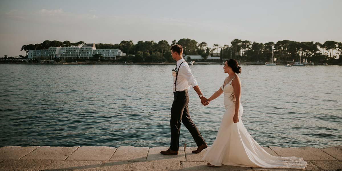 Mladenci koriste predah od njihovog vjenčanja u Hrvastkoj da se fotografiraju uz obalu tijekom zalaska u Poreču.