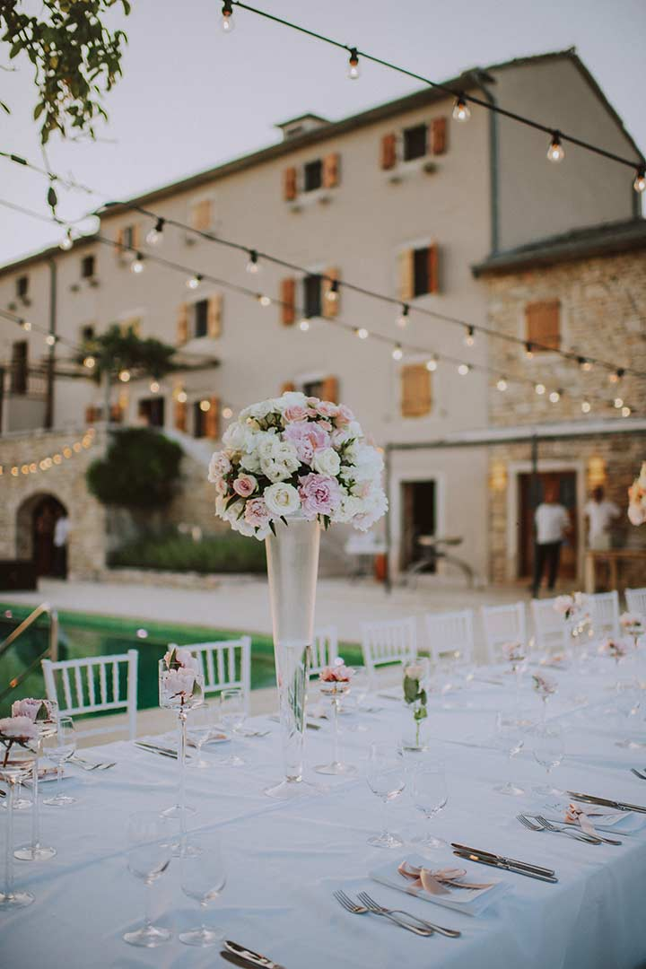 Fully decorated wedding dinner table in front of a rustic villa in the continental Istria.