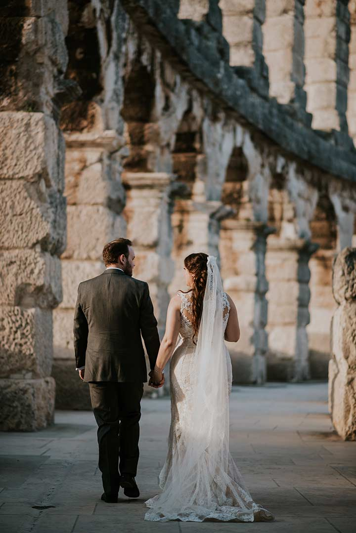 Newlyweds walking along the remains of the amphiteather Arena in Pula, after their wedding in Istria.