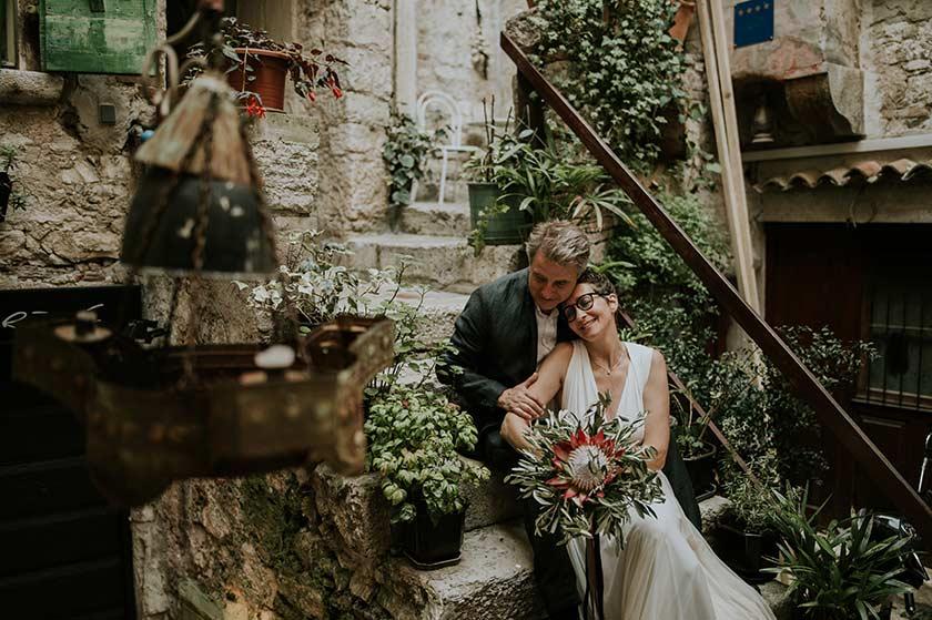 Newlyweds cuddling on a decorated doorstep in Rovinj.