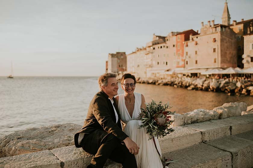 Newlyweds cuddling in front of Rovinj, during sunset.