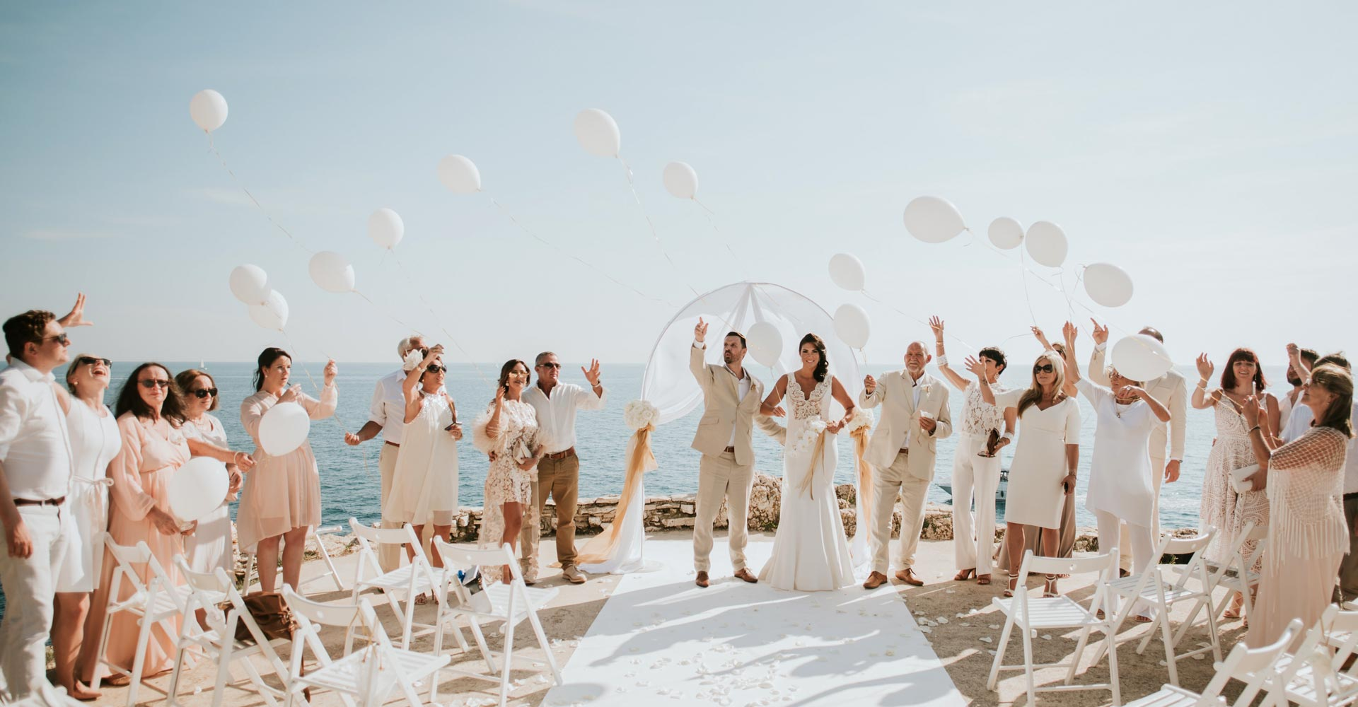 Newlyweds and their closest family and friends celebrate their wedding in                  Croatia, on top of the cliffs at the venue Gates of Paradise, near Adriatic sea.
